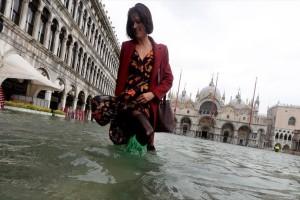 Η φωτογραφία της ημέρας: Μία κοπέλα προσπαθεί να περπατήσει σε πλημμυρισμένη πλατεία της Βενετίας!
