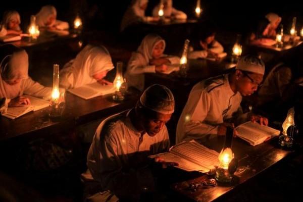 Η Φωτογραφία της Ημέρας: Μαθητές διαβάζουν το Κοράνι με λάμπες πετρελαίου κατά την διάρκεια του Ραμαζανιού