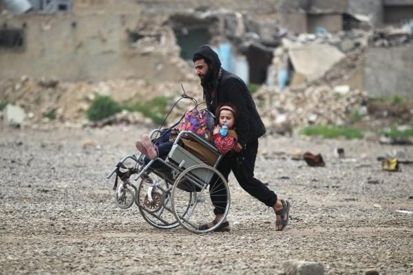 Η Φωτογραφία της Ημέρας: Πατέρας προσπαθεί να σώσει το κοριτσάκι του από την φρίκη του πολέμου στο Ιράκ