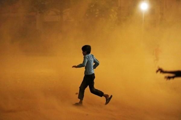 Η φωτογραφία της ημέρας: Ένα αγόρι προσπαθεί να καλυφθεί από αμμοθύελλα στο Νέο Δελχί!