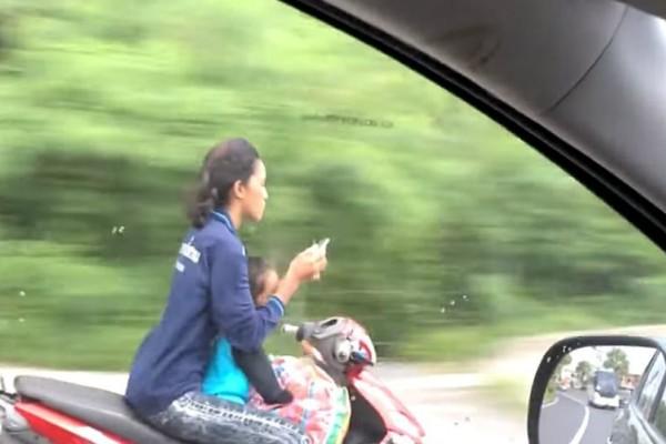 Απαράδεκτο: Μάνα χωρίς κράνος, πληκτρολογεί SMS με παιδί σε μηχανάκι (video)