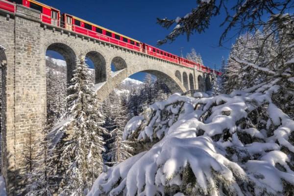 Το κόκκινο τρένο των Χριστουγέννων: Η μαγευτική διαδρομή μέσα από 55 τούνελ και 196 γέφυρες στα χιονισμένα βουνά