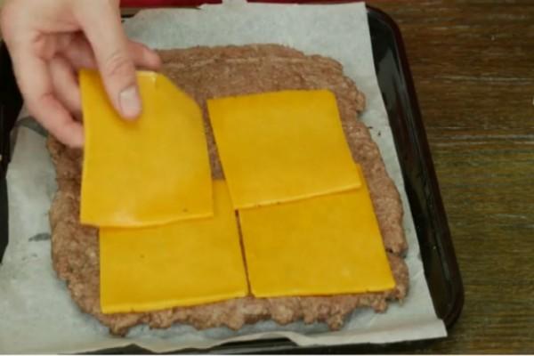 Πάνω σε λαδόκολλα απλώνει κιμά και τον σκεπάζει με τυρί! Θα τρέξετε να το κάνετε!