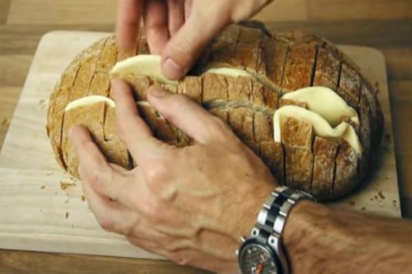 Χαράζει μια φραντζόλα ψωμί και βάζει ανάμεσα τυρί. Με το αποτέλεσμα θα γλείφετε τα δάχτυλά σας!