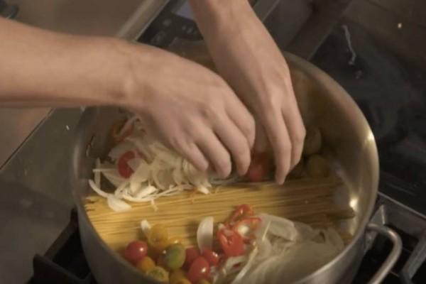 Βάζει τα μακαρόνια στην κατσαρόλα, και προσθέτει κρεμμύδι και ντομάτες…Θα πάθετε πλάκα με την γεύση