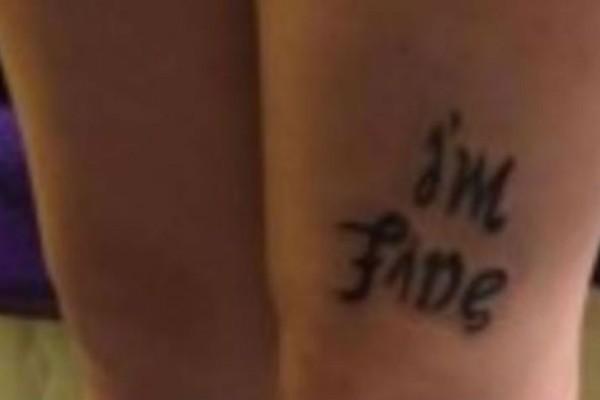 Το τατουάζ στο πόδι της φαίνεται να γράφει