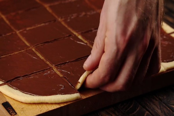 Αλείφει τη ζύμη με νουτέλα και την κόβει σε τετράγωνα κομμάτια - Το τελικό αποτέλεσμα; Ξεπερνά κάθε φαντασία!
