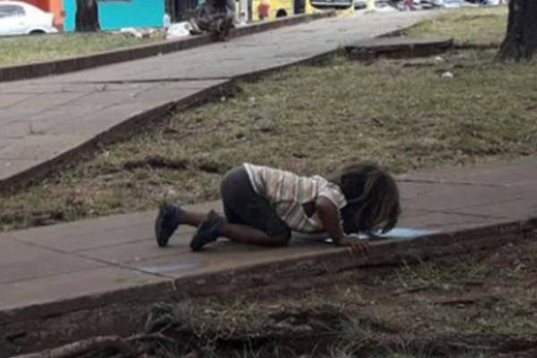 Μικρό παιδί πίνει νερό από λακκούβα σε δρόμο