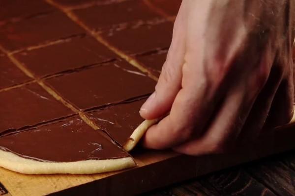 Αλείφει τη ζύμη με σοκολάτα και την κόβει σε τετράγωνα κομμάτια - Το τελικό αποτέλεσμα ξεπερνά κάθε φαντασία!