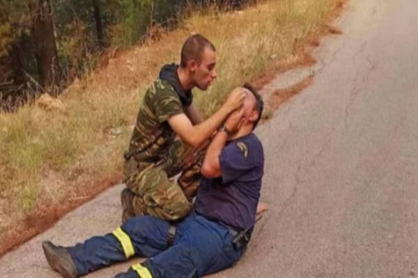 Viral φωτογραφία από τις φωτιές: Στρατιώτης παρέχει τις πρώτες βοήθειες σε πυροσβέστη!