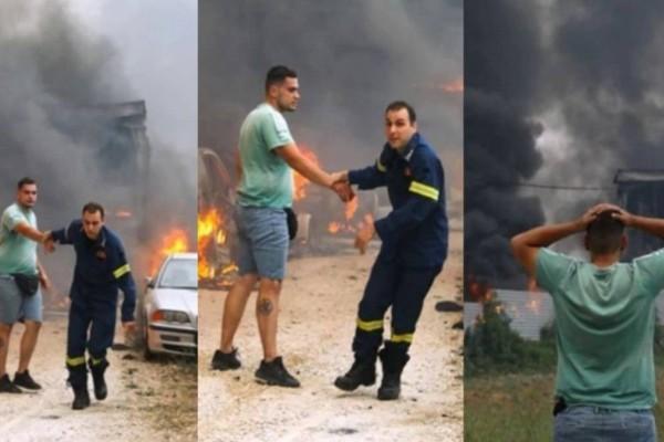 Φωτιά στην Αττική: Πυροσβέστης «παίρνει σηκωτό» ιδιοκτήτη μάντρας αυτοκινήτων που τυλίγεται στις φλόγες