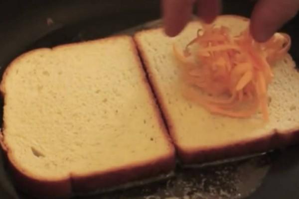 Βάζει 2 φέτες ψωμί στο τηγάνι και προσθέτει τριμμένο τυρί και λάδι - Το αποτέλεσμα θα σας ξετρελάνει