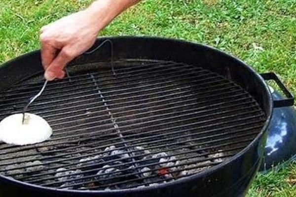 Τρίβει τη σχάρα με κρεμμύδι και μετά ακουμπά τα μπιφτέκια: Ο λόγος θα σας ενθουσιάσει