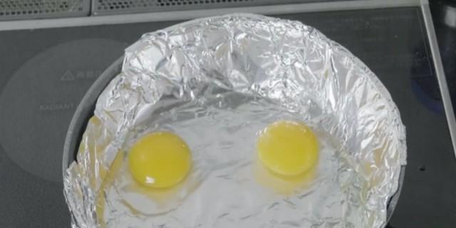 Τυλίγει ένα τηγάνι με αλουμινόχαρτο και ρίχνει μέσα αυγά - Ο λόγος; Πανέξυπνος!