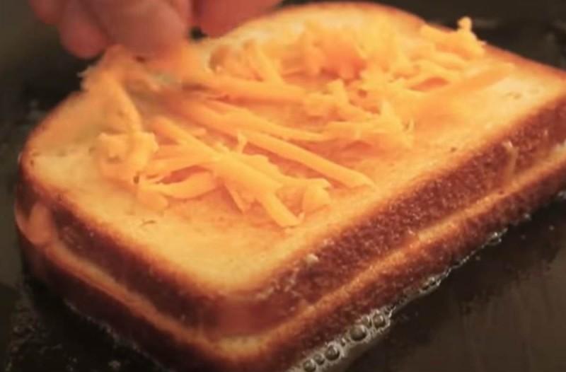 Βάζει 2 φέτες ψωμί στο τηγάνι και προσθέτει λάδι και τυρί - Το αποτέλεσμα θα σας ξετρελάνει