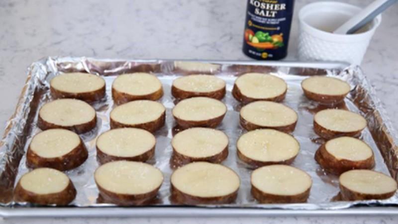 Κόβει πατάτες σε ροδέλες, τις απλώνει στο ταψί και ρίχνει αυτός από πάνω. Το αποτέλεσμα; Πανδαισία γεύσεων